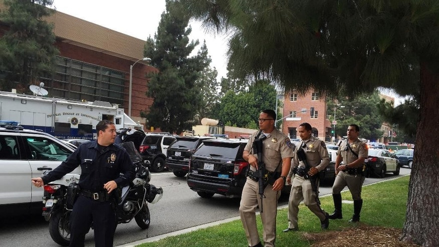 A Los Angeles policeman and Sheriff deputies work at the scene of a fatal shooting at the University of California, Los Angeles, Wednesday, June 1, 2016, in Los Angeles. (AP Photo/Ringo H.W. Chiu)