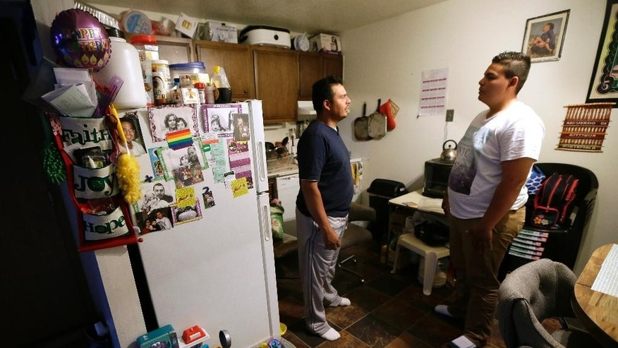 Alejandro Lopez, of Des Moines, Iowa, left, talks with his son Jonathan about his application for asylum, Tuesday, May 10, 2016, in Clive, Iowa. For immigrant children seeking asylum in the U.S., where they apply seems to make a world of difference. (AP Photo/Charlie Neibergall)