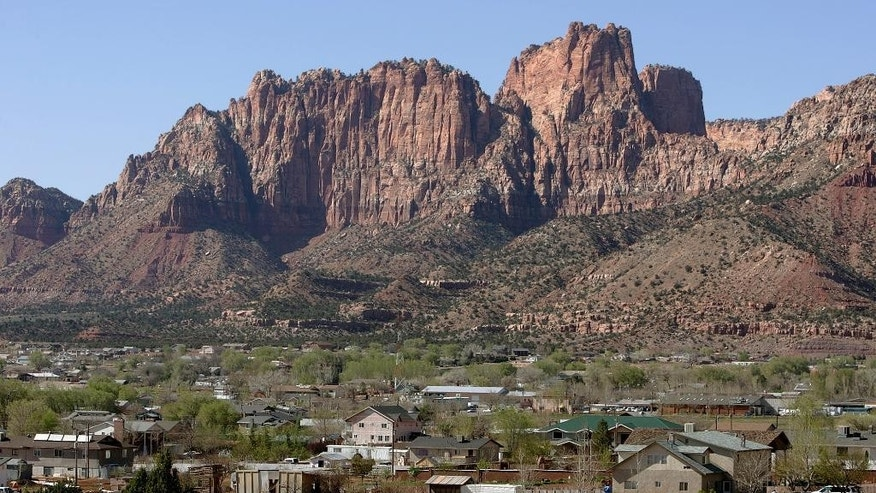 FILE - In this April 20, 2006, file photo, Hildale, Utah, sits at the base of Red Rock Cliff mountains with its sister city, Colorado City, Ariz., in the foreground. The two polygamous towns on the Arizona-Utah line are vigorously opposing a bid to disband their shared police department as a way to remedy religious-based discrimination against nonbelievers, saying problems at the agency don't require such a drastic step. (AP Photo/Douglas C. Pizac, File)