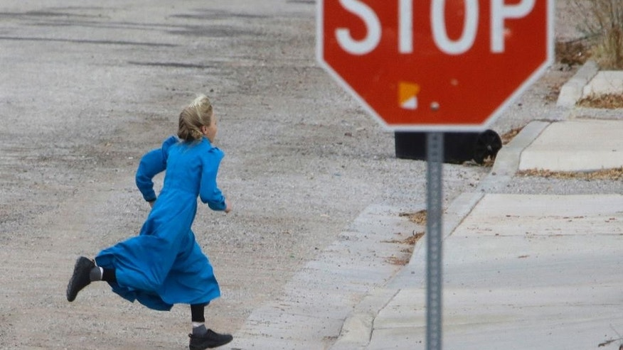 FILE - In this Dec. 16, 2014, file photo, a girl runs past a street sign in Hildale, Utah. The sister cities of Hildale and Colorado City, Ariz., two polygamous towns on the Arizona-Utah border, are vigorously opposing a bid to disband their shared police department as a way to remedy religious-based discrimination against nonbelievers, saying problems at the agency don't require such a drastic step. (AP Photo/Rick Bowmer, File)