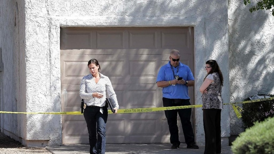 Phoenix police detectives stand outside a home, Thursday, June 2, 2016 in Phoenix where three boys were killed during a several hour period Wednesday night.  The boy's mother was hospitalized in critical condition with self-inflicted stab wounds according to Phoenix police. (AP Photo/Matt York)