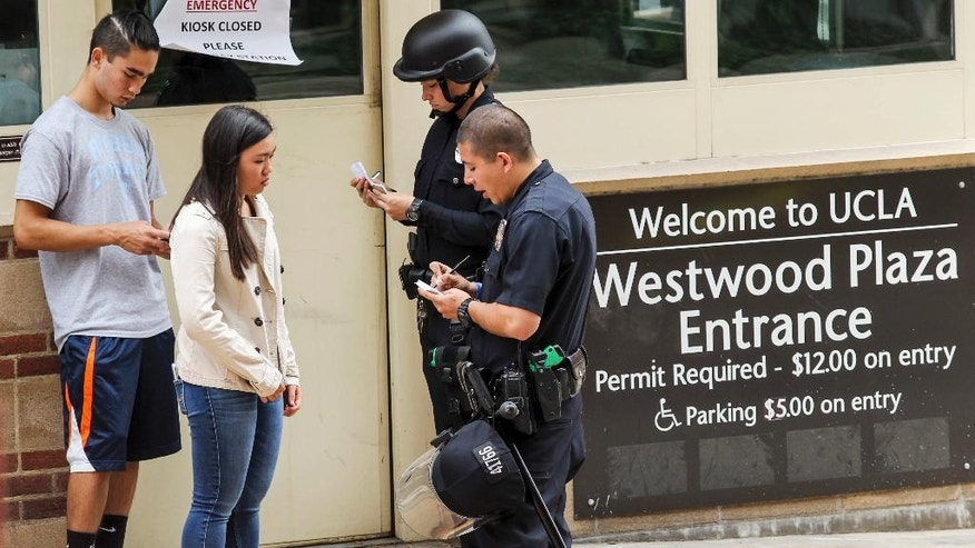 Police officers get information from students at the scene of a fatal shooting at the University of California, Los Angeles, Wednesday, June 1, 2016, in Los Angeles. (AP Photo/Ringo H.W. Chiu)