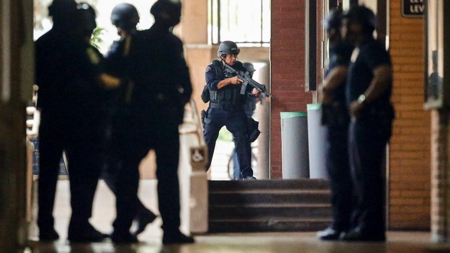 Los Angeles Police officers search the UCLA campus near the scene of a fatal shooting at the University of California, Los Angeles, Wednesday, June 1, 2016, in Los Angeles. Los Angeles police chief says shooting was murder-suicide. (AP Photo/Damian Dovarganes)