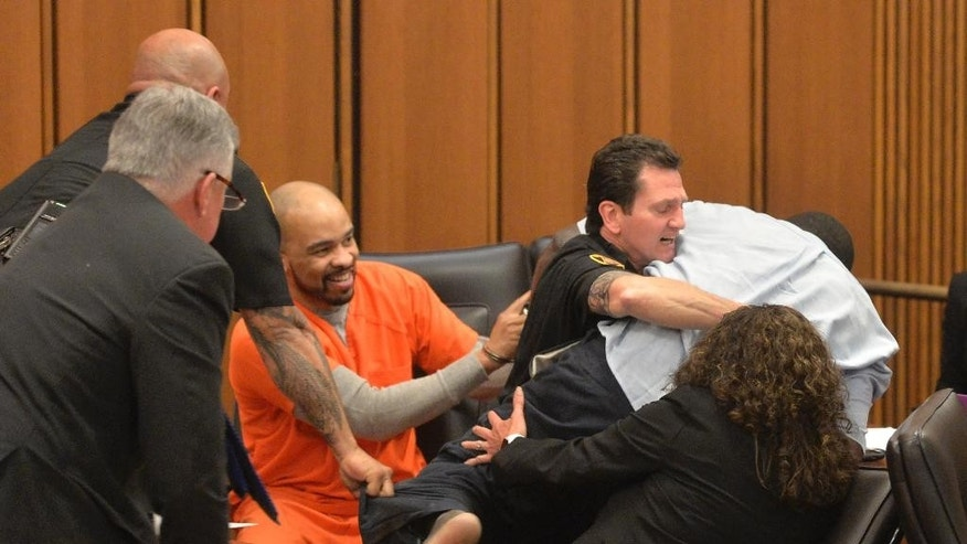A court officer tackles the father of one of three victims of Ohio serial killer Michael Madison, left, who leaped over a table to attack the defendant in court just minutes after the judge pronounced a death sentence in Cuyahoga County Common Pleas Court Thursday, June 2, 2016, in Cleveland. Van Terry, the father of victim Shirellda Terry, was giving testimony about the loss of his daughter when he turned, paused and lunged toward Madison. (AP Photo/David Richard)