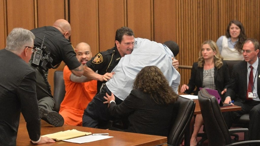 A court officer tackles the father of one of three victims of Ohio serial killer Michael Madison, left, who leaped over a table to attack the defendant in court just minutes after the judge pronounced a death sentence in Cuyahoga County Common Pleas Court Thursday, June 2, 2016, in Cleveland. Van Terry, the father of victim Shirellda Terry, had walked to the front of the courtroom to give a victim-impact statement when he turned, paused and lunged toward Madison, who gave him a malicious smile. (AP Photo/David Richard)