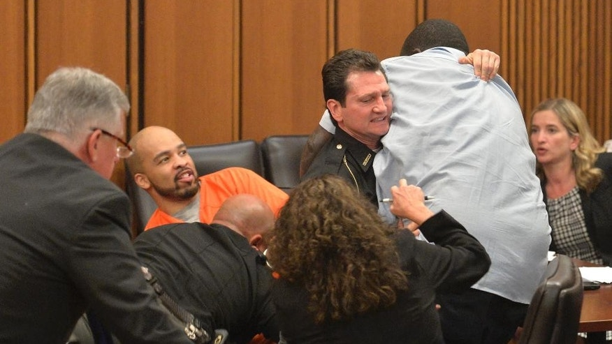 A court officer tackles the father of one of three victims of Ohio serial killer Michael Madison, left, who leaped over a table to attack the defendant in court just minutes after the judge pronounced a death sentence in Cuyahoga County Common Pleas Court Thursday, June 2, 2016, in Cleveland.  (AP Photo/David Richard)
