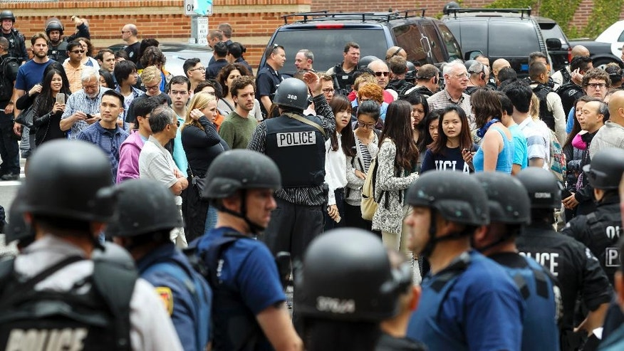 Students and faculty members are escorted by a police officer from the scene of a fatal shooting at the University of California, Los Angeles, Wednesday, June 1, 2016, in Los Angeles. (AP Photo/Ringo H.W. Chiu)
