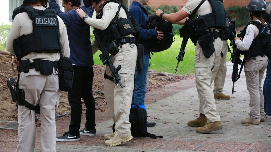 Los Angeles Police officers search students who were evacuated from the Mathematical Sciences Building at the UCLA campus near the scene of a fatal shooting at the University of California, Los Angeles, Wednesday, June 1, 2016, in Los Angeles. (AP Photo/Damian Dovarganes)