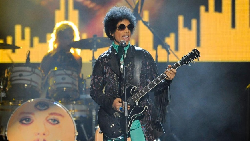 FILE - In this May 19, 2013 file photo, Prince performs at the Billboard Music Awards at the MGM Grand Garden Arena in Las Vegas. A law-enforcement official says that tests show the music superstar died of an opioid overdose. Prince was found dead at his home on April 21, 2016, in suburban Minneapolis. He was 57.  (Photo by Chris Pizzello/Invision/AP, File)