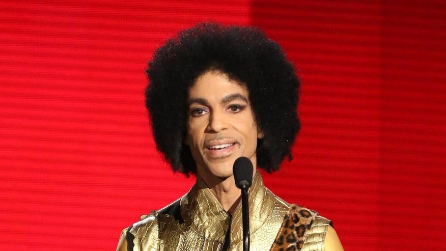 FILE - In this Nov. 22, 2015 file photo, Prince presents the award for favorite album - soul/R&B at the American Music Awards in Los Angeles. A law-enforcement official says that tests show the music superstar died of an opioid overdose. Prince was found dead at his home on April 21, 2016, in suburban Minneapolis. He was 57. (Photo by Matt Sayles/Invision/AP, File)