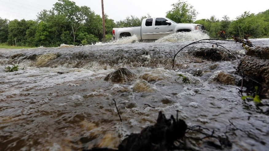A motorist passes through a low-water crossing near New Braunfels, Texas, Thursday, June 2, 2016. About half of Texas is under flood watches or warnings, including Fort Bend County, southwest of Houston, where about 1,400 homes have been affected by the swollen Brazos River. (AP Photo/Eric Gay)