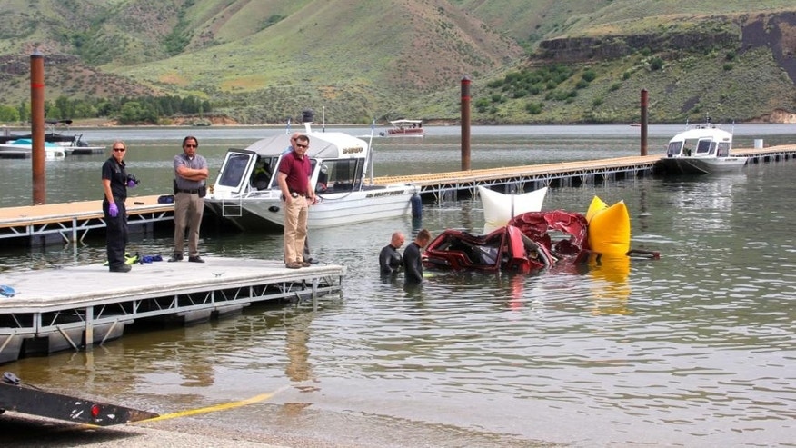 In this photo provided by the Ada County Sheriff's Office, Ada County Sheriff's Deputies and divers with the Boise Fire Department stand by the wreckage of an SUV driven by a 40-year-old Boise woman that plunged off a cliff into the Lucky Peak Reservoir Thursday, June 2, 2016, in Boise, Idaho. Divers with the Boise Fire Department recovered the bodies of two girls, ages 12 and 6, and the body of a 10-year-old boy from the vehicle, which was about 40 feet below the surface Thursday morning, according to the Ada County Sheriff's Office. A witness saw the SUV accelerate from the side of the road to go over the cliff, the sheriff's office said. (Patrick Orr/Ada County Sheriff's Office via AP)
