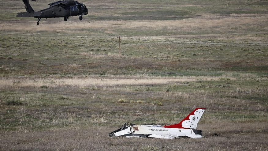 Crew inside a military helicopter examine the site where a U.S. Air Force Thunderbird crashed following a flyover performance at a commencement for Air Force Academy cadets, south of Colorado Springs, Colo.,  Thursday, June 2, 2016. The pilot ejected safely from the jet. (AP Photo/Brennan Linsley)