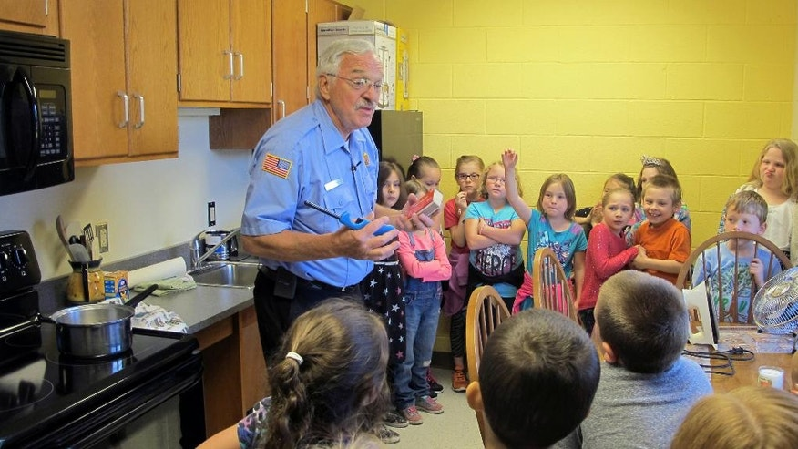 In this May 20, 2016 photo, Dewittville Volunteer Fire Department Chief Burl Swanson tells second-graders about kitchen fire hazards during a field trip to Chautauqua Children's Safety Education Village in Ashville, N.Y. The not-for-profit is one of dozens of safety villages in the United States and Canada and more are in the works, including one near Albany, N.Y., the idea being that learning by doing in a safe environment is the best defense against real danger. (AP Photo/Carolyn Thompson)