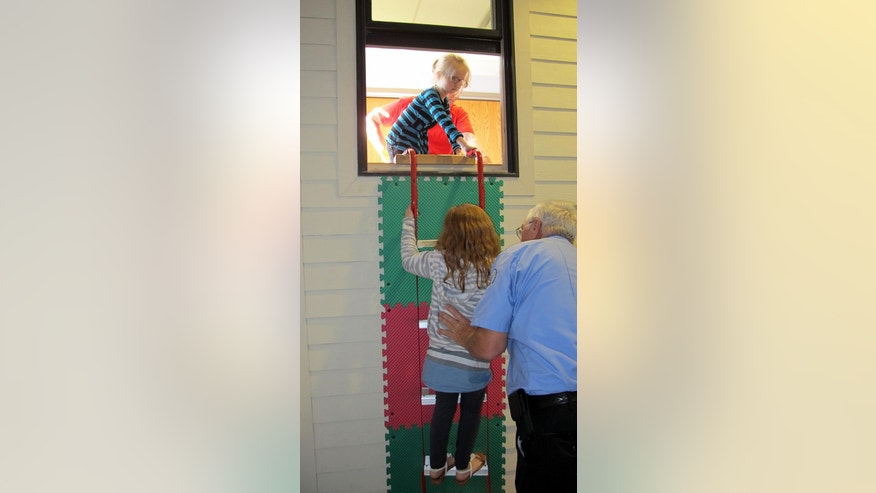 In this May 20, 2016 photo, Dewittville Volunteer Fire Department Chief Burl Swanson helps second-graders from Bush Elementary School practice climbing down a fire escape ladder during a field trip to Chautauqua Children's Safety Education Village in Ashville, N.Y. The not-for-profit is one of dozens of safety villages in the United States and Canada and more are in the works, including one near Albany, the idea being that learning by doing in a safe environment is the best defense against real danger. (AP Photo/Carolyn Thompson)
