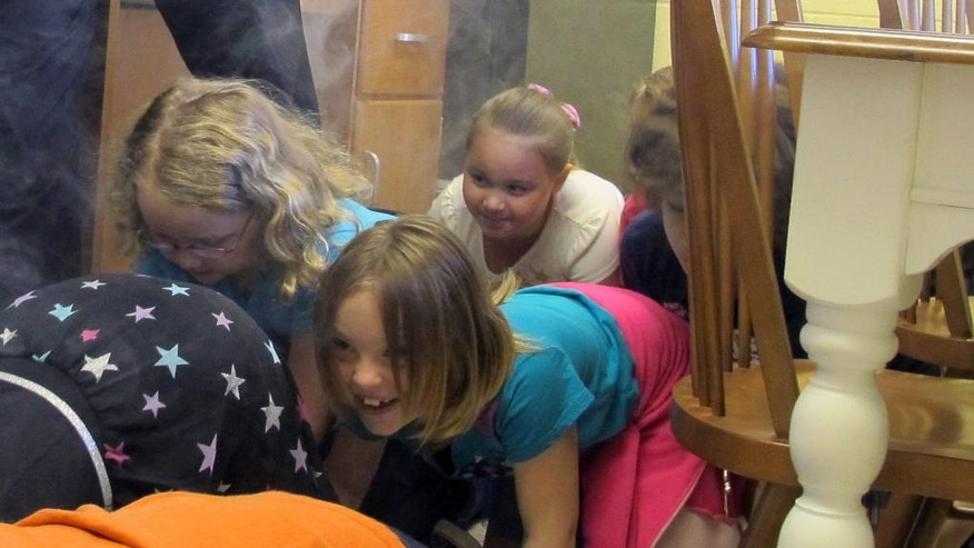 In this May 20, 2016 photo, second-graders from Bush Elementary School crawl under smoke from a simulated kitchen fire during a field trip to Chautauqua Children's Safety Education Village in Ashville, N.Y. The not-for-profit is one of dozens of safety villages in the United States and Canada and more are in the works, including one near Albany, N.Y., the idea being that learning by doing in a safe environment is the best defense against real danger. (AP Photo/Carolyn Thompson)