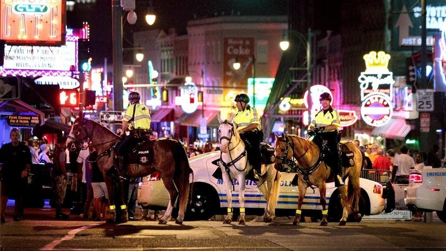 In this late Saturday, June 4, 2016, photo, Memphis Police Department mounted police close off Beale Street so investigators can work the scene where Officer Verdell Smith was struck by the fleeing vehicle of a man suspected in a downtown shooting, in Memphis, Tenn. Smith died at Regional Medical Center. (Nikki Boertman/The Commercial Appeal via AP) MANDATORY CREDIT