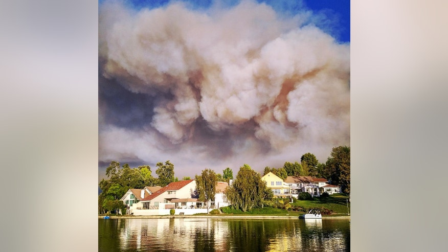 This photo provided by Matthew Dangerfield shows billowing smoke  from the Calabasas, Calif., fire as the clouds passed over the homes of Park Calabasas, Saturday, June 4, 2016. Los Angeles County fire officials now say a brushfire in the Calabasas neighborhood is threatening about 3,000 homes. Capt. Keith Mora tells KCAL-TV that's how many are near the 200-acre blaze that erupted Saturday afternoon northwest of downtown Los Angeles. He says about 200 homes and some 500 people are under mandatory evacuation but the others are strongly urged to leave the area, where flames up to 50 feet high rolled along ridgetops and torched trees right next to million-dollar homes.  (Matthew Dangerfield via AP)