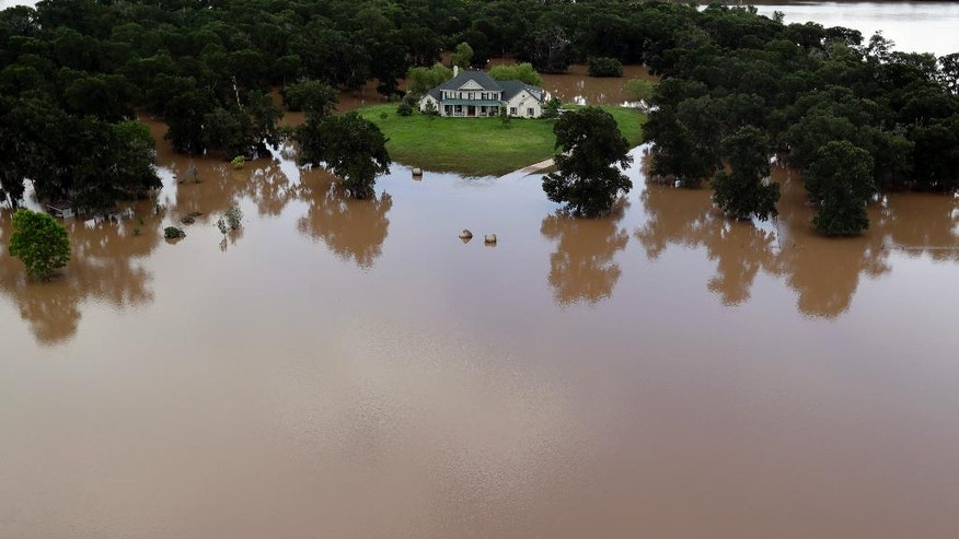 A home surrounded by floodwaters is shown in this aerial view Saturday, June 4, 2016, near Richmond, Texas. Parts of Texas have been inundated with rain in the last week, and more than half of the state has been under flood watches or warnings. (AP Photo/David J. Phillip)