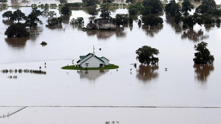 Homes surrounded by floodwaters are shown in this aerial view, Saturday, June 4, 2016, in Rosharon, Texas. Parts of Texas have been inundated with rain in the last week, and more than half of the state has been under flood watches or warnings. (AP Photo/David J. Phillip)