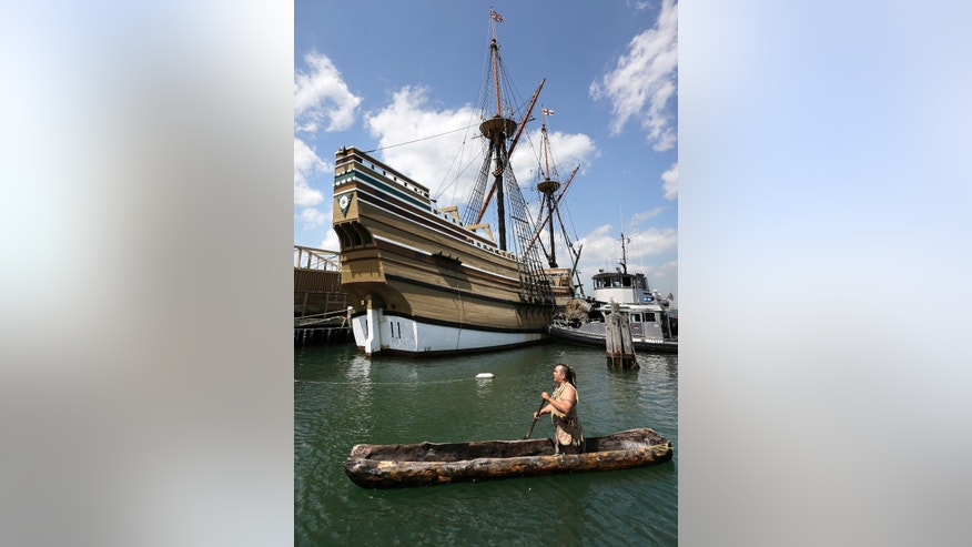 Darius Coombs, a Mashpee Wampanoag Native American, of Mashpee, Mass., paddles past the Mayflower II,  moments after the ship arrived in Plymouth Harbor, Monday, June 6, 2016, in Plymouth, Mass. The 1957 replica of the famed ship that carried the Pilgrims to Massachusetts in 1620 has been undergoing an extensive restoration at the Henry B. DuPont Preservation Shipyard, at Mystic Seaport, in Mystic, Conn., in the run-up to Plymouth's 400th anniversary in 2020. Coombs met the Mayflower II in the harbor to commemorate the ships arrival. (AP Photo/Steven Senne)