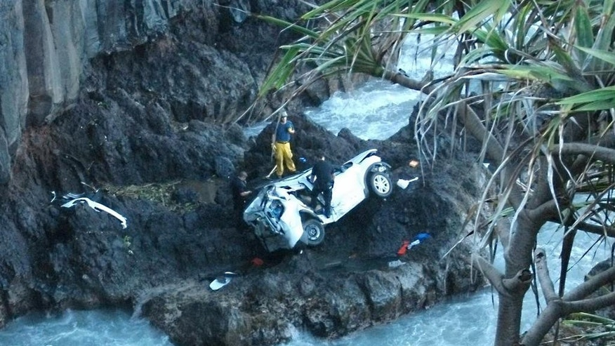 In this May 29, 2016 photo provided by Vicki Sawyer, rescue workers respond to the scene of a car crash off Maui's Hana Highway in Hana, Hawaii. A Maui woman who was driving the vehicle when it plunged off the cliff is charged with murder in the death of her twin, who was in the passenger's seat. Prosecutors say Alexandria Duval, who is also known as Alison Dadow, intentionally caused the death of her sister, Anastasia Duval, also known as Ann Dadow. The 37-year-old sisters were traveling on Hana Highway when their Ford Explorer crashed into a rock wall last week. (Vicki Sawyer via AP)