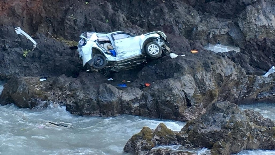 In this May 29, 2016 photo provided by Tom Johnson, a vehicle sits at the bottom of a cliff off Maui's Hana Highway in Hana, Hawaii. A Maui woman who was driving the vehicle when it plunged off the cliff is charged with murder in the death of her twin, who was in the passenger's seat. Prosecutors say Alexandria Duval, who is also known as Alison Dadow, intentionally caused the death of her sister, Anastasia Duval, also known as Ann Dadow. The 37-year-old sisters were traveling on Hana Highway when their Ford Explorer crashed into a rock wall last week. Police say the Explorer fell about 200 feet. (Tom Johnson via AP)