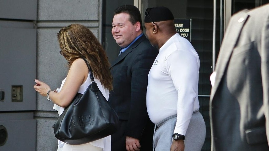 FILE - In this May 25, 2016, file photo, Eliseo Perez, center, an assistant chief for security at the Rikers Island correctional facility, leaves Criminal Court in the Bronx borough of New York. Perez is among five New York jail employees, including a correction department chief, who were convicted Tuesday, June 7, of attempted assault charges for allegedly beating an inmate who stared down the chief during a search of his cell at Rikers Island in June 2012. (AP Photo/Frank Franklin II, File)