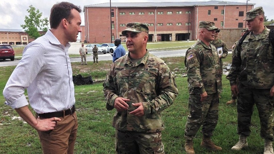 U.S. Army Secretary Eric Fanning, left, receives a briefing from Army Col. Benjamin DiMaggio about his battalion's basic combat training course for new soldiers at Fort Jackson, South Carolina on Tuesday, June 7, 2016. Fanning is the new civilian leader of the Army and the first opening gay individual to lead one of the nation's military services. Fanning visited Fort Jackson and is making the first stop on a number of visits he intends to make to U.S. military installations in the United States and overseas in the coming months. (AP Photo/Susanne M. Schafer)
