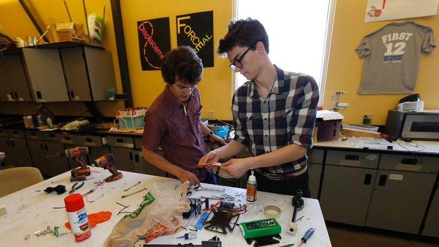 In this photo taken Friday, April 22, 2016, Nathan Lapore, right, and Max Alger-Meyer work on their drone at DSST Stapleton in Denver. Alger-Meyer, a Denver teen who visited Rwanda's Akagera National Park last summer, had an idea he thought would make the rangers' job easier: a drone. He and a friend have built one to donate to the park. (AP Photo/David Zalubowski)