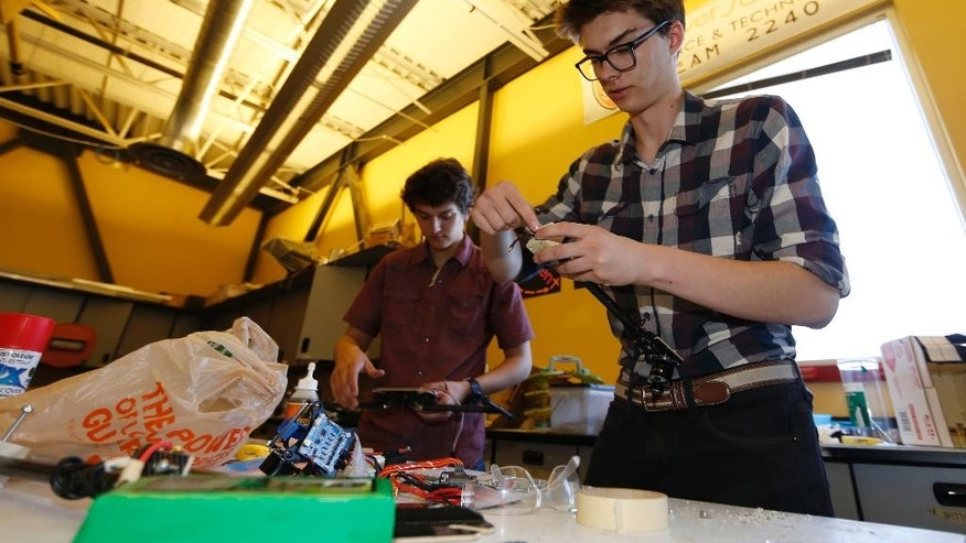 In this photo taken Friday, April 22, 2016, Nathan Lapore, right, and Max Alger-Meyer work on a drone at DSST Stapleton in Denver. Alger-Meyer, a Denver teen who visited Rwanda's Akagera National Park last summer, had an idea he thought would make the rangers' job easier: a drone. He and a friend have built one to donate to the park. (AP Photo/David Zalubowski)