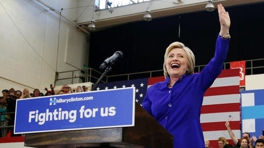 """Democratic presidential candidate Hillary Clinton, left, reacts as she takes the stage at a rally, Monday, June 6, 2016, in Long Beach, Calif. Eight years after conceding she was unable to """"shatter that highest, hardest glass ceiling,"""" Hillary Clinton is embracing her place in history as she finally crashes through as the presumptive Democratic presidential nominee. (AP Photo/John Locher)"""