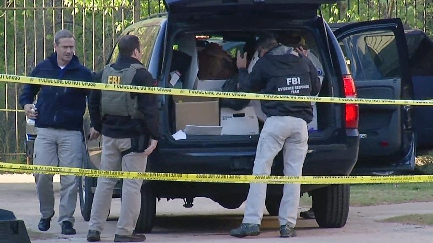 FILE - In this April 10, 2014, file photo taken from video, FBI agents collect evidence at an apartment complex in Atlanta, where federal agents rescued kidnap victim Frank Janssen, of Wake Forest, N.C. Kelvin Melton, a violent criminal described as a high-ranking member of the Bloods street gang goes on trial Monday, June 6, 2016, in North Carolina on a federal kidnapping charge after authorities say he helped orchestrate the abduction of Janssen, a prosecutor's father, from his prison cell. (AP Photo/Johnny Clark, File)