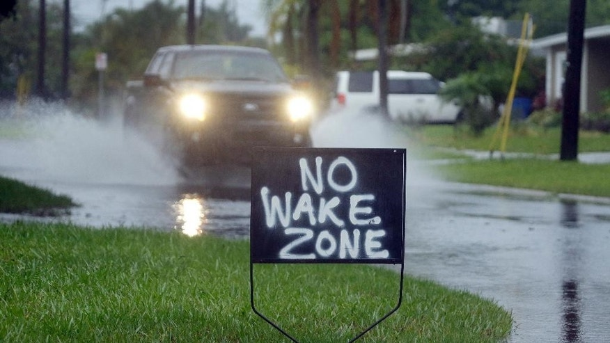 A resident of Shore Acres in St. Petersburg, Fla., has a sign urging motorists to slow down on flooded streets Tuesday, June 7, 2016. Remnants of Tropical Storm Colin continued to dump rain along Florida's gulf coast Tuesday. (AP Photo/Chris O'Meara)