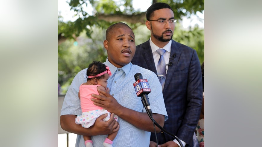 Isaiah Baskins, center, holds his daughter Ka'leigh Baskins as he speaks as attorney Justin Bamberg, right, listens during a news conference in Winston-Salem, N.C., Wednesday, June 8, 2016. Isaiah Baskins and Katie Thomas were subjected to a racial rant by a volunteer at the Wake Forest Baptist Medical Center that Baskins recorded.  Bamberg, representing the family of Isaiah Baskins, says he's negotiating with the hospital to ensure such incidents aren't repeated.   (AP Photo/Chuck Burton)