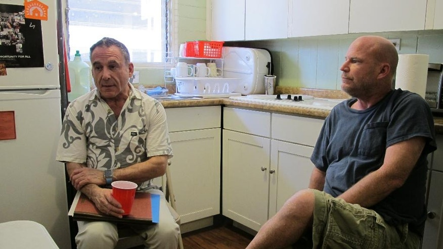 In this Wednesday, May 18, 2016 photo, Jonathon Berliner, left, executive director of Gregory House Programs, and David Willett, a resident, talk in the kitchen of Gregory House in Honolulu. Shelter managers in Hawaii are scrambling to figure out how to keep a roof over the heads of hundreds of homeless people. Similar cuts are being made around the country as the federal Department of Housing and Urban Development shifts its money to programs that focus on permanent housing. (AP Photo/Cathy Bussewitz)