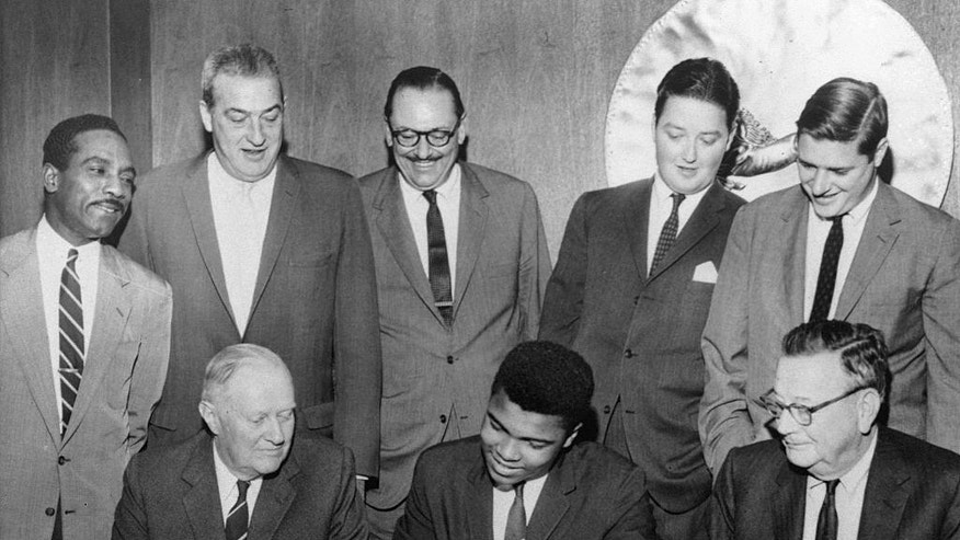 FILE - In this Oct. 27, 1960 file photo, Cassius Clay, center, 1960 Olympic boxing champion, signs a professional contract accompanied ten outstanding businessmen in Louisville, Ky. Among those at the signing, standing, left to right, Cassius Clay, Sr., the boxer's father; Wm. Faversham, Jr.; W.L. Lyons Brown, Sr.; James Ross Todd; and George Norton, IV, all of Louisville, Kentucky. Seated are, left to right, Patrick Calhoun, Jr., Goshen, Ky.; Clay and Vertner D. Smith, Sr., Louisville. Ali's interest in the Nation began in his high school years in Louisville, when he lived under the yoke of Jim Crow laws, even after returning home with an Olympic gold medal in 1960. (H.B. Littell/The Courier-Journal via AP) NO SALES; MAGS OUT; NO ARCHIVE; MANDATORY CREDIT