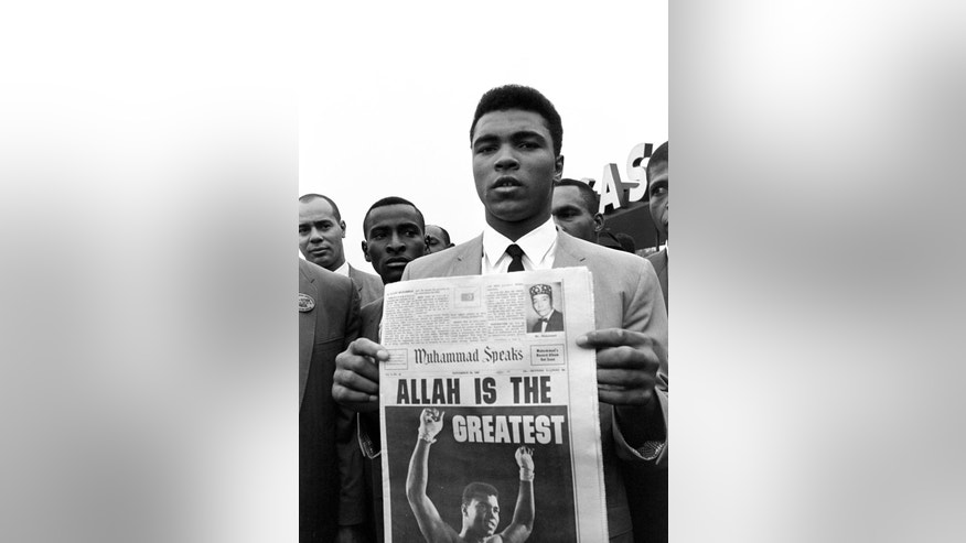 "FILE - In this Nov. 22, 1965 file photo, heavyweight champion Muhammad Ali, holds a ""Muhammad Speaks"" newspaper bearing his picture as he and followers of the Muslim sect leave the Las Vegas convention center after weigh-in ceremonies to defend his title against challenger Floyd Patterson. In a 1964 interview with The Associated Press in which he formally declared himself a Muslim, Ali said he didn't like the phrase ""Black Muslims,"" and described Islam as ""the true way to save the world, which is on fire with hate."" He declared ""forced and token integration"" was a ""pacifier,"" or temporary solution to problems blacks face, and one group should not impose its culture on another. (AP Photo/Sal Veder)"