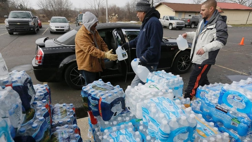 FILE - In this Feb. 5, 2016 file photo, volunteers load a vehicle with bottled water at Our Lady of Guadalupe Church, in Flint, Mich. Flint's lead-contaminated water crisis has affected all of the city's nearly 100,000 residents, but some grapple with an extra challenge: A language barrier. Advocates residents who speak little or no English say some didn't learn about the water problems - or need for filters - for months after the problems became known. (AP Photo/Carlos Osorio, File)
