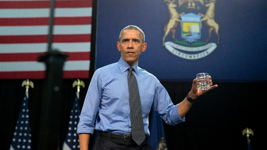 FILE - In this May 4, 2016 file photo, President Barack Obama holds up a glass of water he will drink from, after speaking at Flint Northwestern High School about the ongoing water crisis, in Flint, Mich. Flint's lead-contaminated water crisis has affected all of the city's nearly 100,000 residents, but some grapple with an extra challenge: A language barrier. Obama, who declared a state of emergency in the city in mid-January and ordered federal aid to supplement the state and local response, visited Flint in May. (AP Photo/Carolyn Kaster, File)