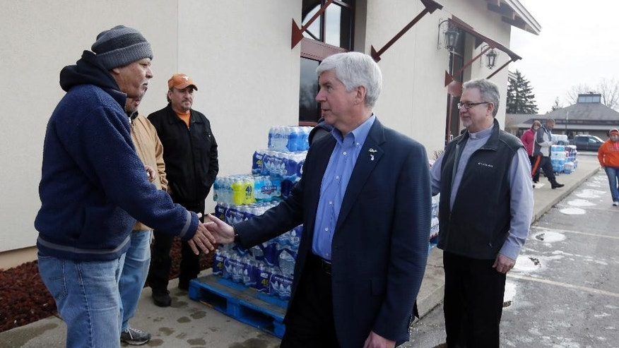 FILE - In this Feb. 5, 2016 file photo, Michigan Gov. Rick Snyder, center, and Our Lady of Guadalupe Church Deacon, Omar Odette, meets with volunteers helping to load vehicles with bottled water, in Flint, Mich. Snyder visited the church that's distributing water and filters to its predominantly Latino parishioners. Our Lady of Guadalupe Church north of the city developed bilingual information with government officials. (AP Photo/Carlos Osori, File)
