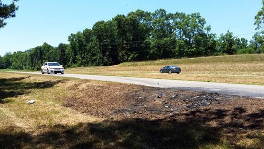Cars pass charred ground, Tuesday, June 7, 2016, remnants at the scene of a fatal traffic accident  in rural Tuscaloosa County, Ala. James Halsell Jr., a former NASA astronaut who flew on five space shuttle missions, is is charged with murder after an early-morning car wreck Monday, June 6, killed two young sisters on the lonely stretch of highway in Alabama. (AP Photo/Phillip Lucas)