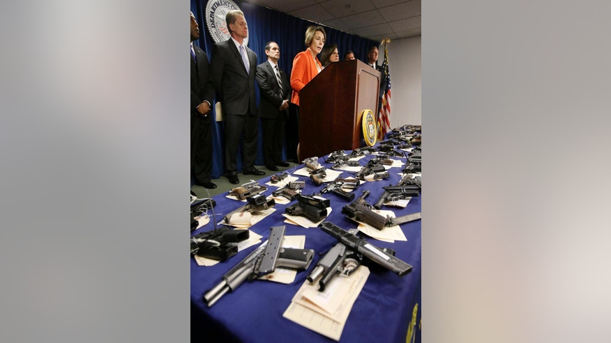 Massachusetts Attorney General Maura Healey, top center, responds to questions from reporters while standing behind a table covered with guns during a news conference at the federal courthouse, Thursday, June 9, 2016, in Boston. Law enforcement officials say more than 60 alleged gang members from Boston and other cities in eastern Massachusetts have been charged with drug, weapons and racketeering charges. Officials said the firearms displayed at the news conference were seized during the investigation. (AP Photo/Steven Senne)