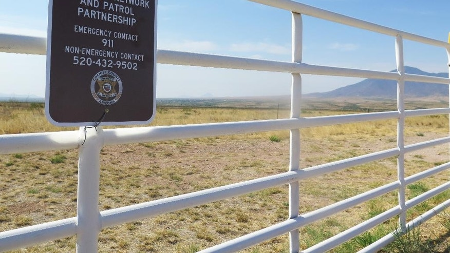 A sign from the Cochise County Sheriff's Department hangs in front of the San Jose Ranch, which shares 10 miles with the U.S.-Mexico border in southern Arizona near Naco, Ariz., on Thursday, June 9, 2016. Ranch owner John Ladd is one of about 30 border ranchers who received police radios from the Cochise County Sheriff's Department this week so that they could more easily communicate with 911 when they are in remote areas that have poor cell phone signal. The ranchers say that drug smugglers and other criminals frequently cross through their land, putting them in danger.  (AP Photo/Astrid Galvan)