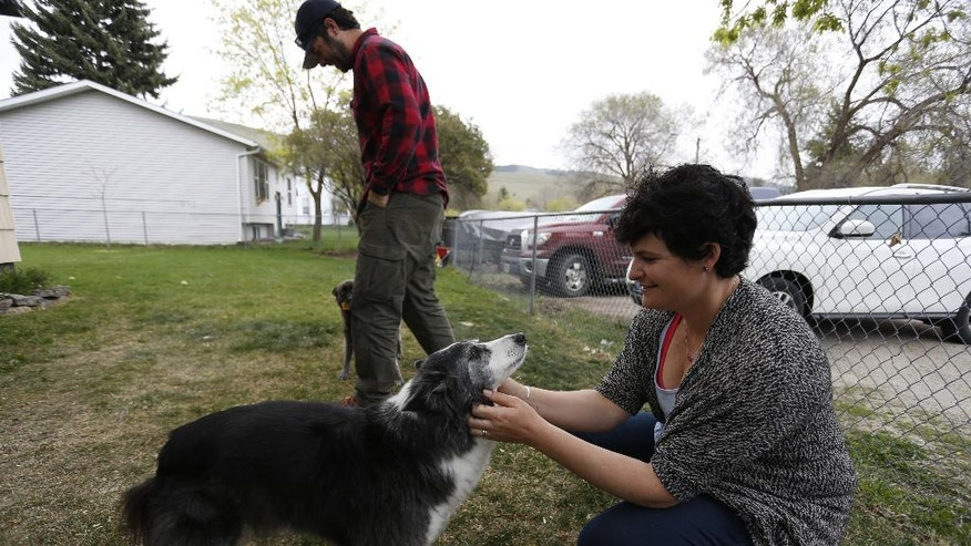 "In this April 14, 2016 photo, activist and Soft Landing founder Mary Poole plays with her dog at home in Missoula, Mont. Haunted by the 2015 photo of a Syrian refugee boy washed ashore in Turkey, she and members of her book group asked: Why not bring a small number of Syrian families to Missoula? ""It wasn't even a grain of sand in my brain that people wouldn't want to help starving, drowning families. I didn't do this to be controversial. I didn't do this to stir the pot,"" she says. (AP Photo/Brennan Linsley)"