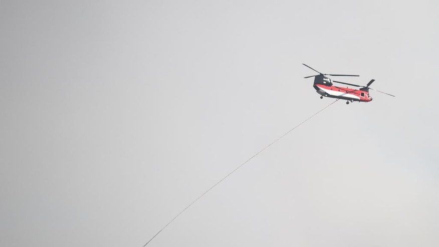 A helicopter aids in the effort to extinguish a brush fire in Yarnell, Ariz., Wednesday, June 8, 2016. The brush fire threatened structures Wednesday in the north-central Arizona town of Yarnell — the scene of a 2013 wildfire in which 19 members of an elite firefighting crew were killed. Some residents on the town's east and west sides were being told to evacuate their homes as a precaution, Yavapai County sheriff's officials said. (Les Stukenberg/The Daily Courier via AP) MANDATORY CREDIT