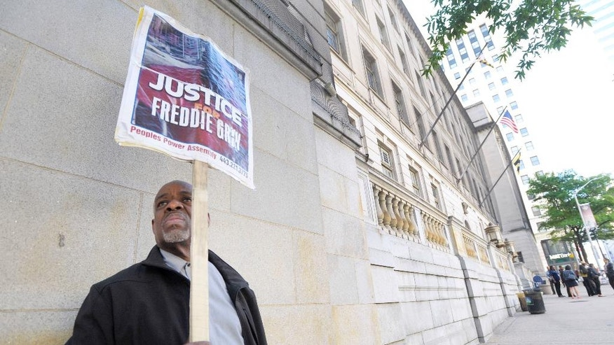 Arthur B. Johnson Jr., of Baltimore, demonstrates alone outside Baltimore's Courthouse East on the first day of the trial of Officer Caesar Goodson, not pictured, one of six Baltimore city police officers charged in connection to the death of Freddie Gray, in Baltimore, Thursday, June 9, 2016. Goodson, the driver of the transport wagon that carried Gray after his arrest, faces second-degree murder, manslaughter and other charges. (AP Photo/Steve Ruark)