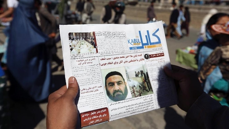 FILE - In this May 25, 2016, file photo, an Afghan man reads a local newspaper with photos the former leader of the Afghan Taliban, Mullah Akhtar Mansoor, who was killed in a U.S. drone strike in Kabul, Afghanistan. A senior U.S. defense official says the administration is moving toward a decision to expand the military's authority to conduct airstrikes against the Taliban in Afghanistan. The official says a final decision has not been made. But there is a broad desire to give the military greater ability to help the Afghan forces. (AP Photo/Rahmat Gul, File)