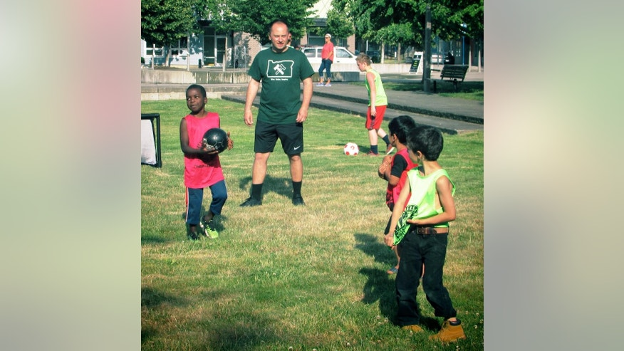 In this photo taken Wednesday, June 8, 2016,  Portland Thorns coach Mark Parsons plays with children in an event with 4 Worlds United Soccer Alliance in Portland, Ore. The organization seeks to welcome refugee and immigrant children through soccer. (AP Photo/Anne M. Peterson)