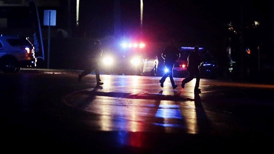 Police investigate the scene of a shooting from the intersection of Hwy 22 and Columbia Road on Thursday, June 9, 2016, in Landen, Ohio. Authorities say two people have been shot including a sheriff's deputy, and the alleged gunman remains on the loose. The shooting happened Thursday night in Deerfield Township, about 25 miles northeast of Cincinnati. (Sam Greene/The Cincinnati Enquirer via AP)  MANDATORY CREDIT;  NO SALES